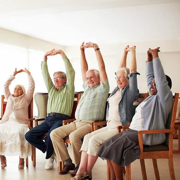 A group of older adults participates in a group fitness class
