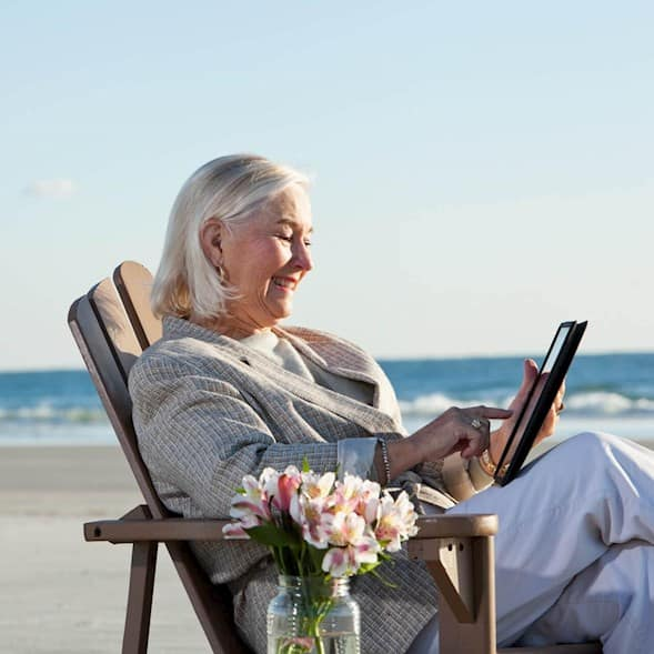 An older woman sits on the beach using her tablet