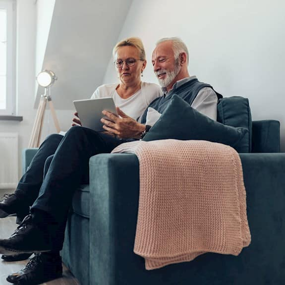 An older couple using a digital tablet to surf the internet