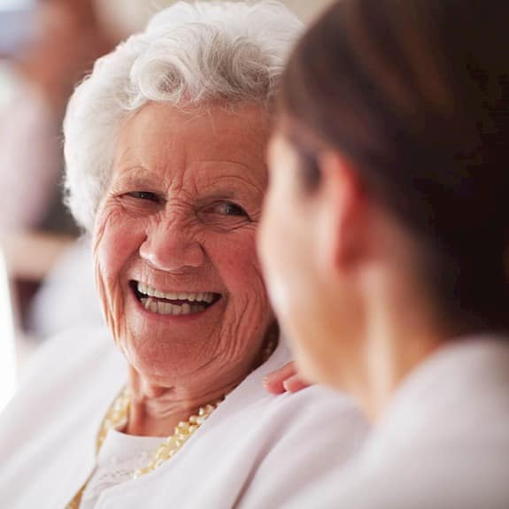 An older woman smiling at a younger woman