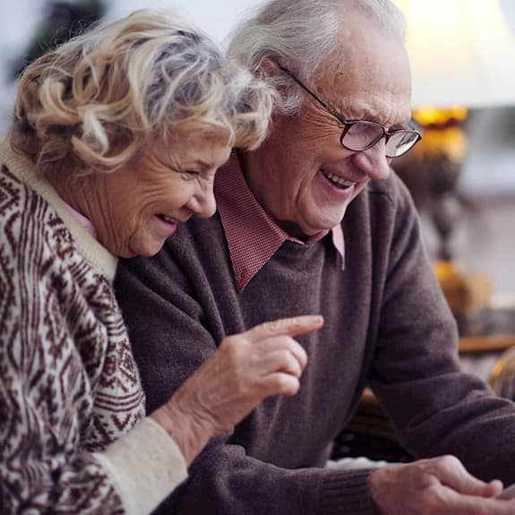 An older couple using a digital tablet at home
