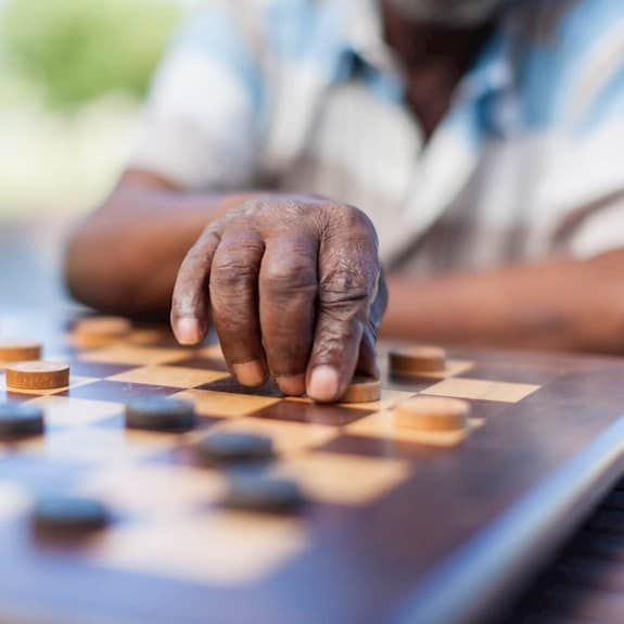 An older man playing chess, about to make a move
