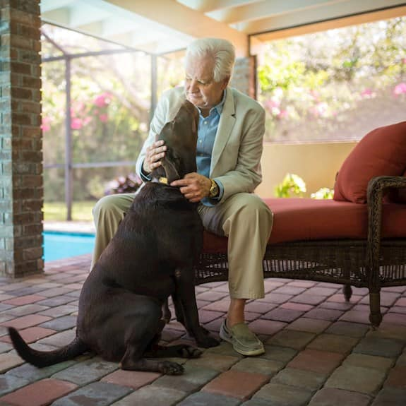 An older man with his chocolate lab
