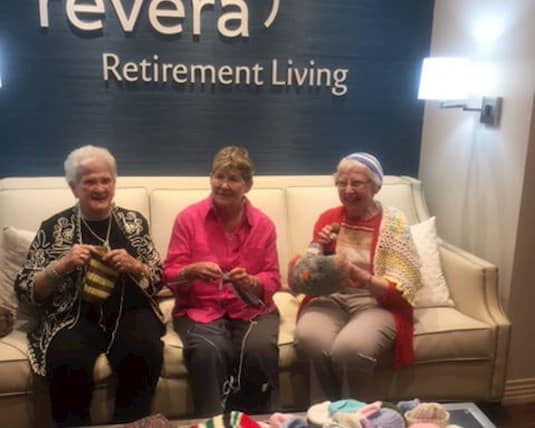 Three older women sitting on a couch, knitting, surrounded by completed knitting projects.