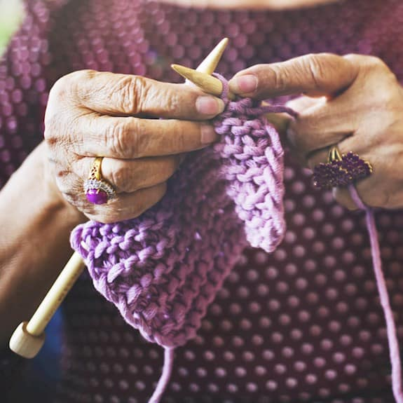 A cropped image of an older woman knitting