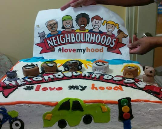 "A photo of a cake and sign that read ""Neighbourhoods"" and ""#lovemyhood"""