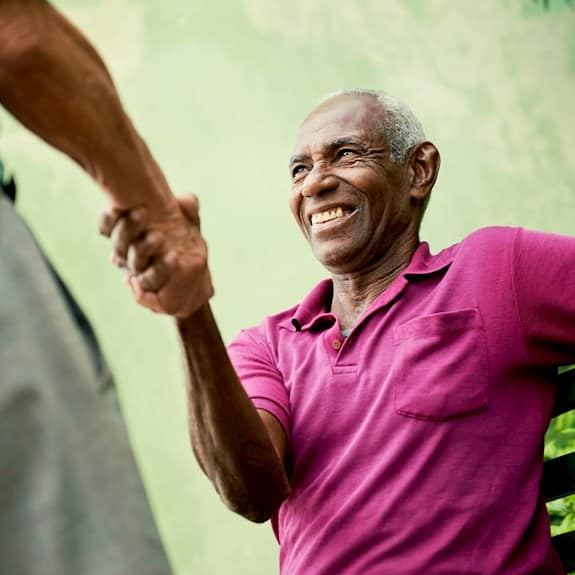 An older man shakes hands with someone