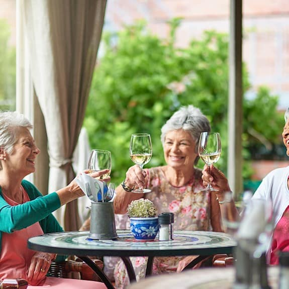 A group of older women enjoying a glass of wine together