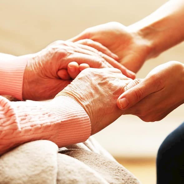 Cropped photo of a younger adult holding the hands of an older woman