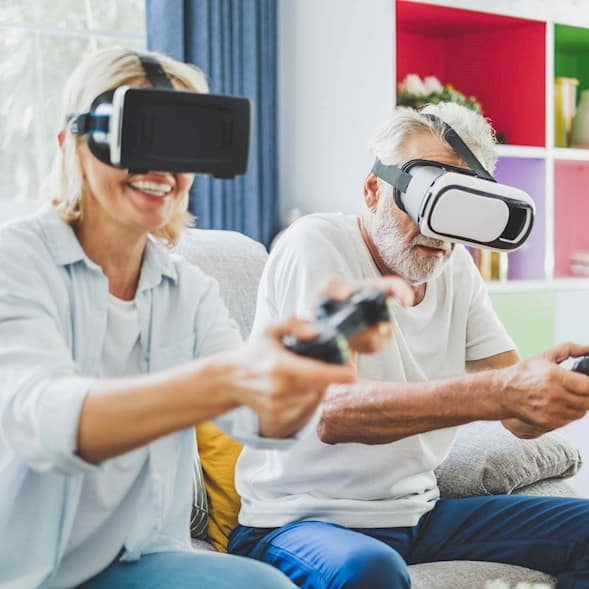 An older couple using VR headsets to play a video game