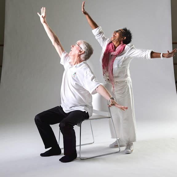 An older man sits in a chair, with an older woman behind him. Both have their arms outstretched in a dancing pose