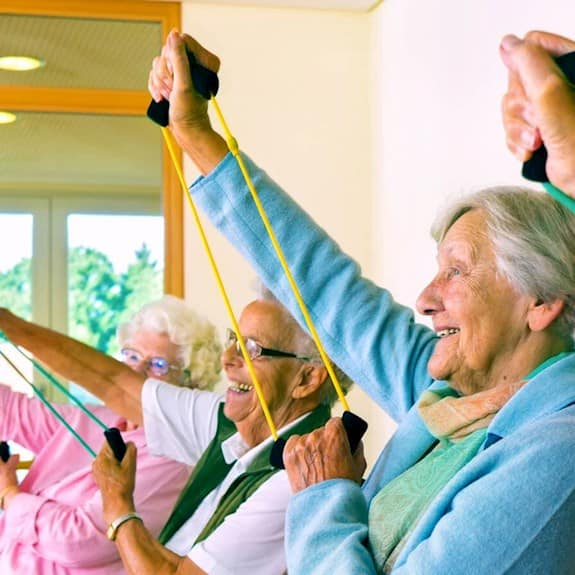 Older adults participating in a fitness class using strengthening bands