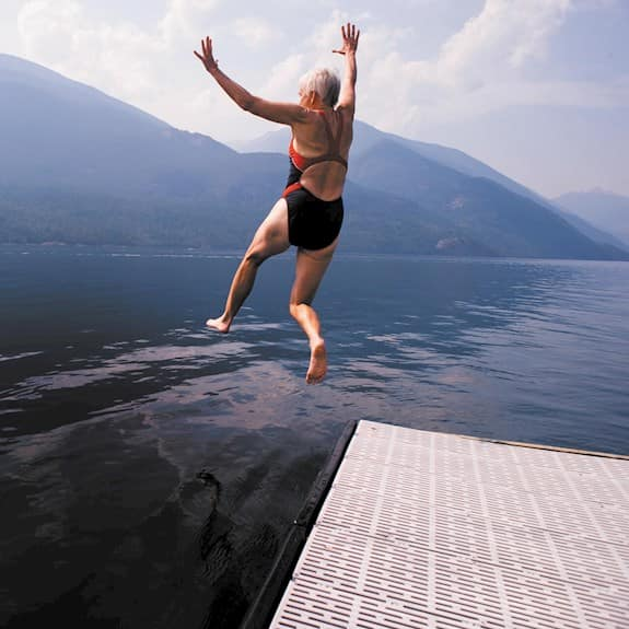 An older woman jumping into a lake