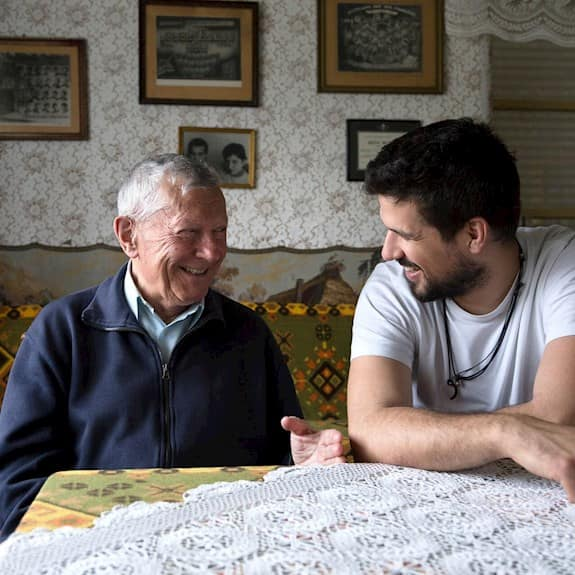 Grandfather And His Grandson Talking And Laughing While Spending Time Together