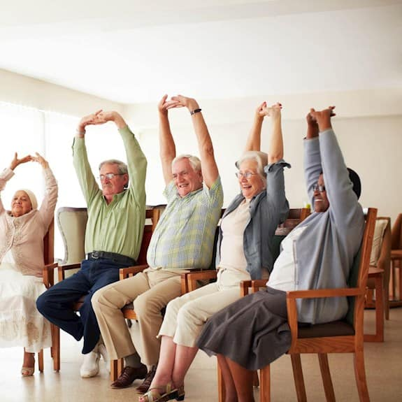 Daily stretching exercise routine for a group of cheerful older adults