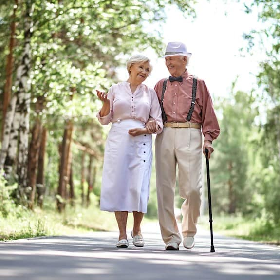 An older couple walking in the woods