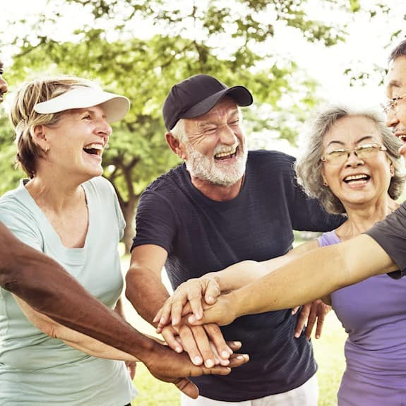A group of older adults in exercise clothing smiling and stacking their hands together