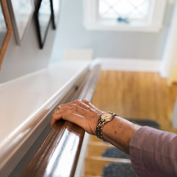 Close-up shot of an older woman's hand on a stair railing