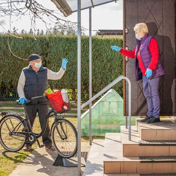 A man standing beside a bicycle, wearing personal protective equipment, waves at a woman wearing personal protective equipment standing by her open door.