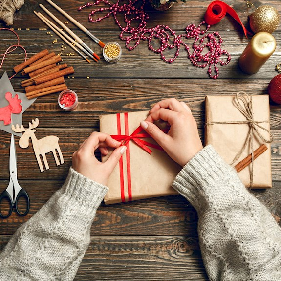 Girl in a sweater wrapping a Christmas present