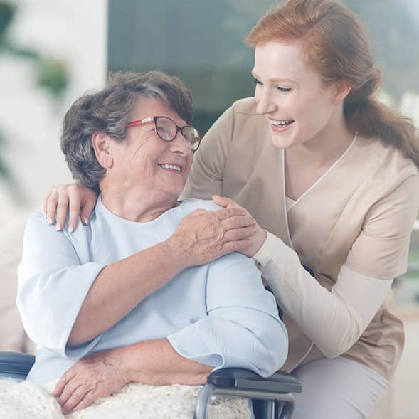 An older woman in a wheelchair is smiling and holding the hand of the younger femal caregiver who is crouching behind her