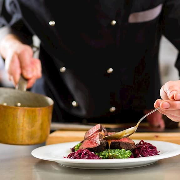 A chef pouring sauce on a plate with meat and vegetables