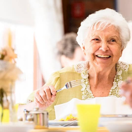 An older woman sitting at the dining table smiling at her companion