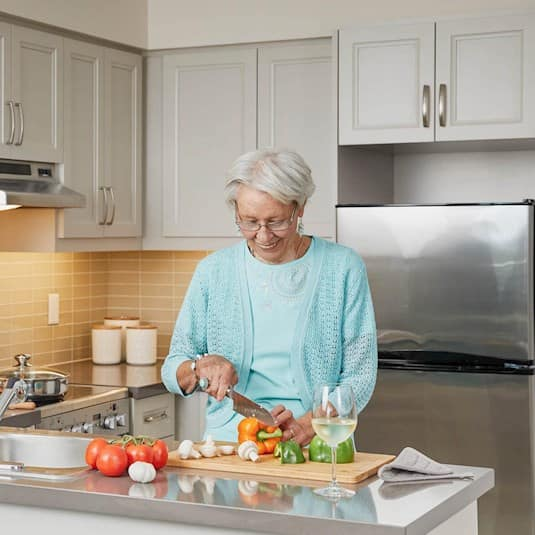 An older woman smiling while cutting vegetables in her kitchen