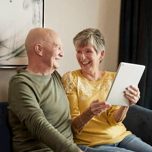 An older couple laughing while the woman holds an electronic tablet