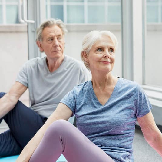 An older couple participates in a yoga class
