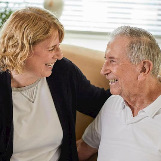 A male senior and a female family member smile at each other
