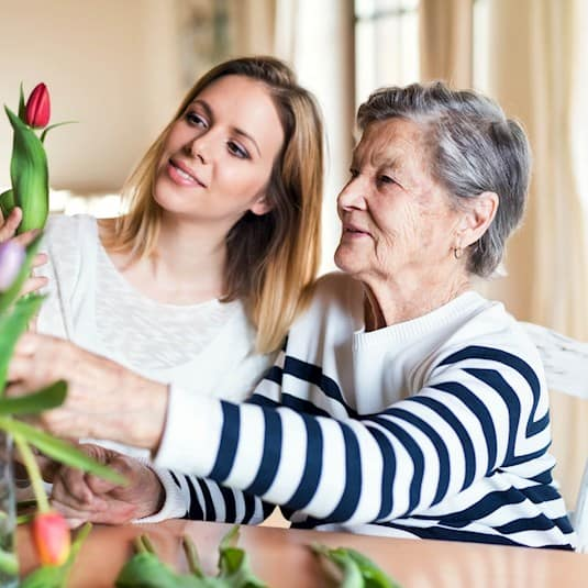 senior and family member arranging flowers