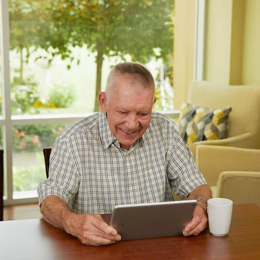 An older man sitting at a table looking at an electronic tablet