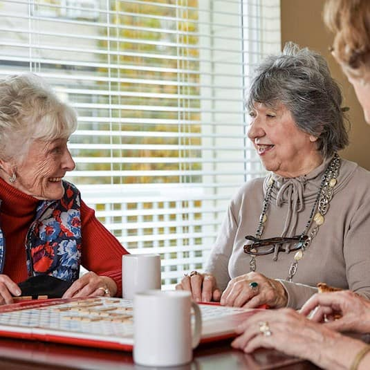 Three women sitting at a table together enjoying coffee, cake and a game of scrabble