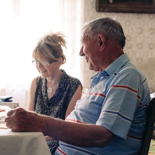 senior and family member sitting at the table