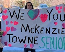 """A volunteer and her three daughters hold a sign reading """"We love you McKenzie Towne Seniors"""""""
