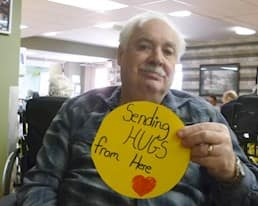 """A resident holds a sign that reads """"Sending HUGS from here"""""""