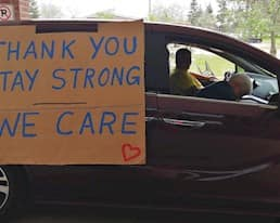 """A van with a sign reading """"Thank you, stay strong, we care"""" taped to the outside drives past a residence"""