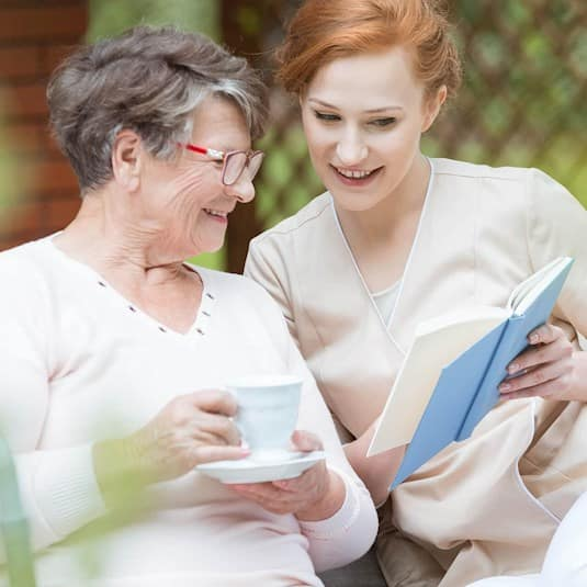 senior with caregiver reading