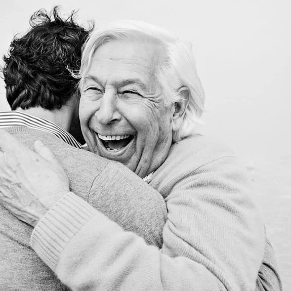 An older man smiling and hugging a younger man