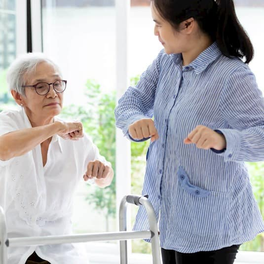 A senior woman working with a caregiver