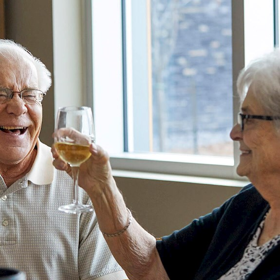 A man and a woman laugh and raise their glasses in a toast