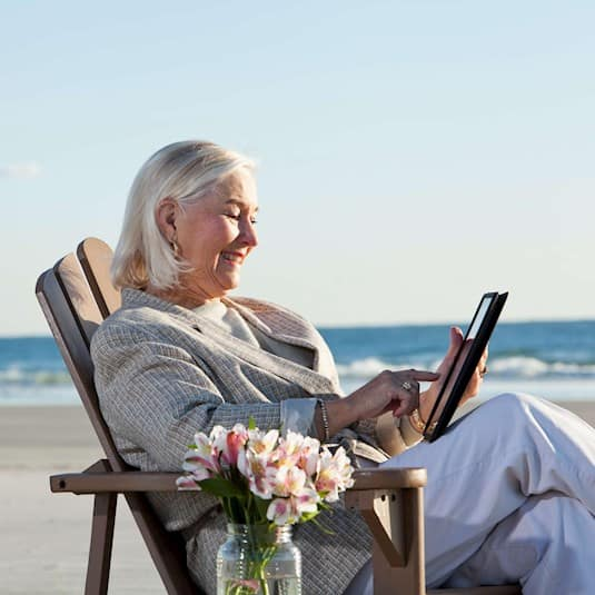 Woman on a beach reading on her tablet