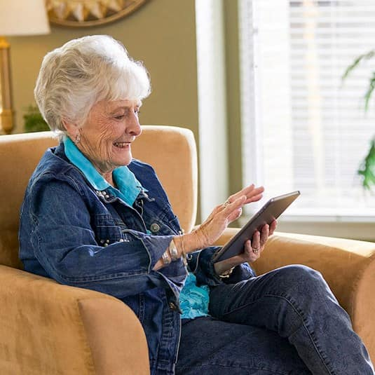 A woman sits in a chair using an electronic tablet