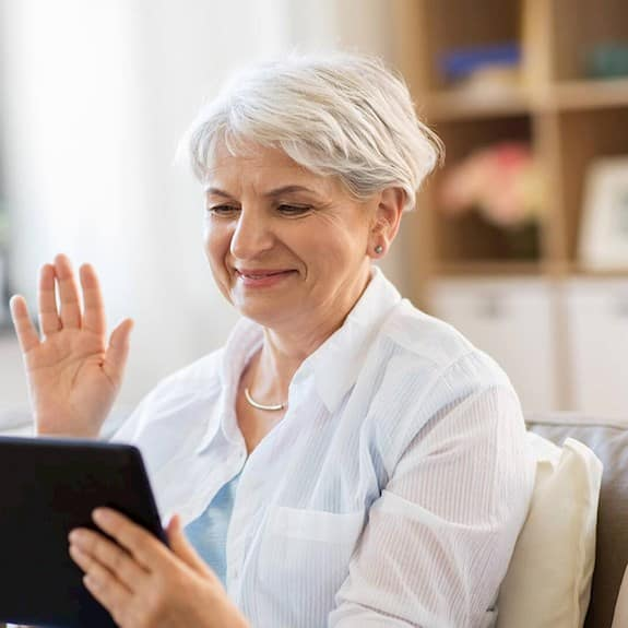 An older woman on an iPad smiles and waves