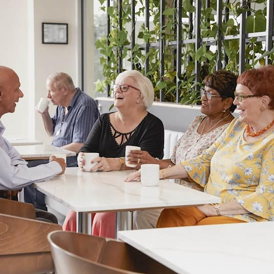 Seniors laughing and enjoying a coffee