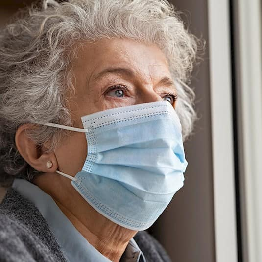 An older woman wearing a mask looks out the window