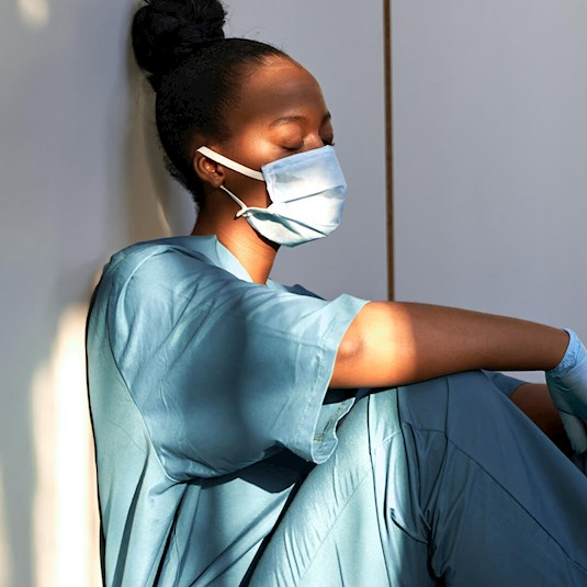 An exhausted caregiver wearing a mask and gloves sits against the side of a building