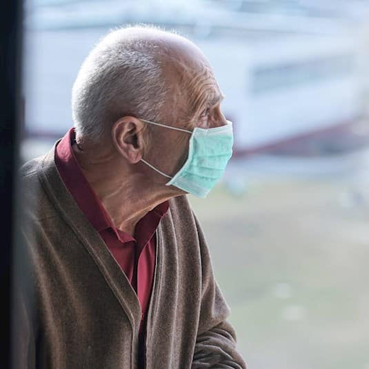 An older man wearing a mask looks out the window