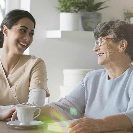 A senior and caregiver enjoying coffee and talking
